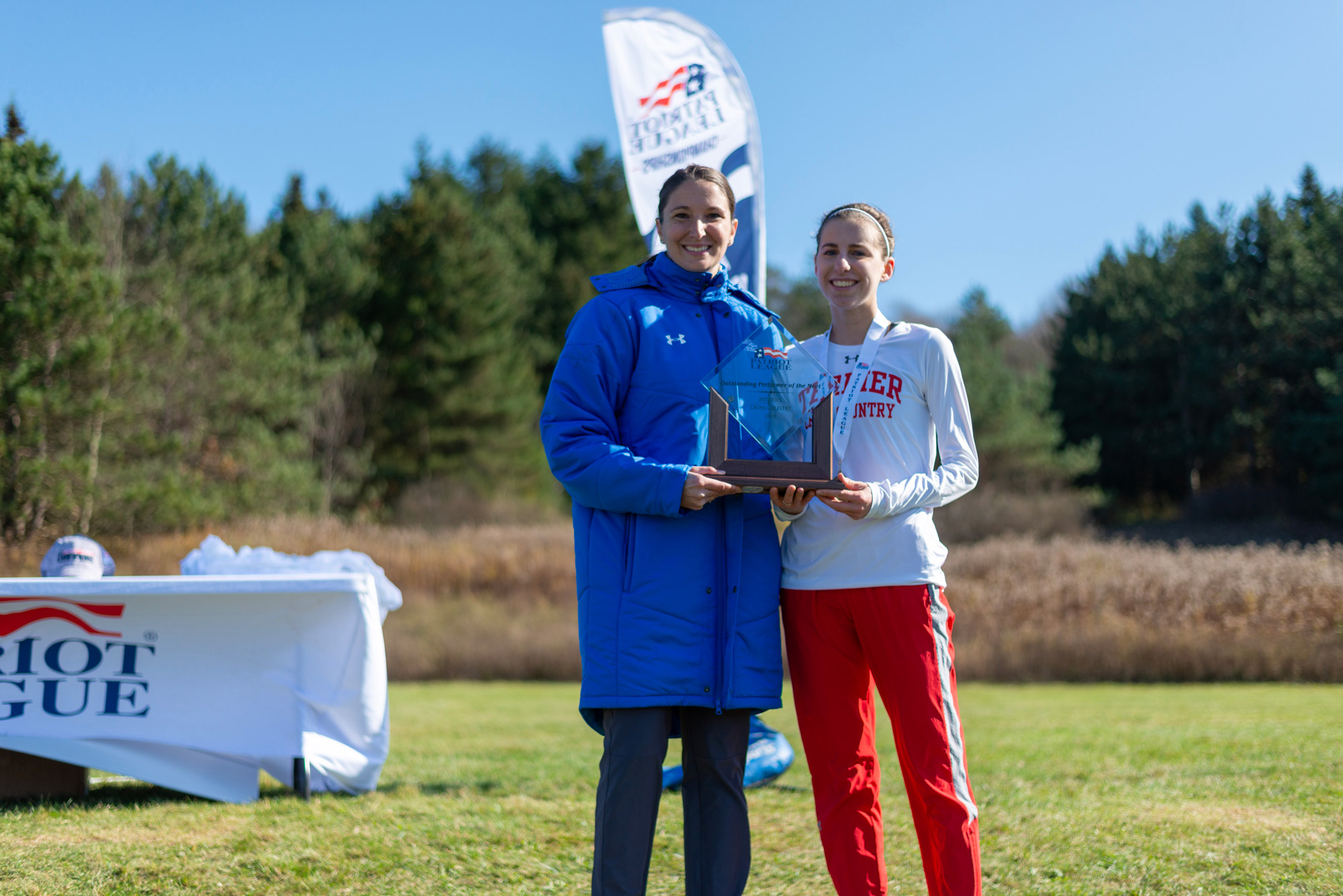 Abigail Gugel holds her award while standing next to Emily Parkins, Director for Championships and Sport Management for the Patriot League.