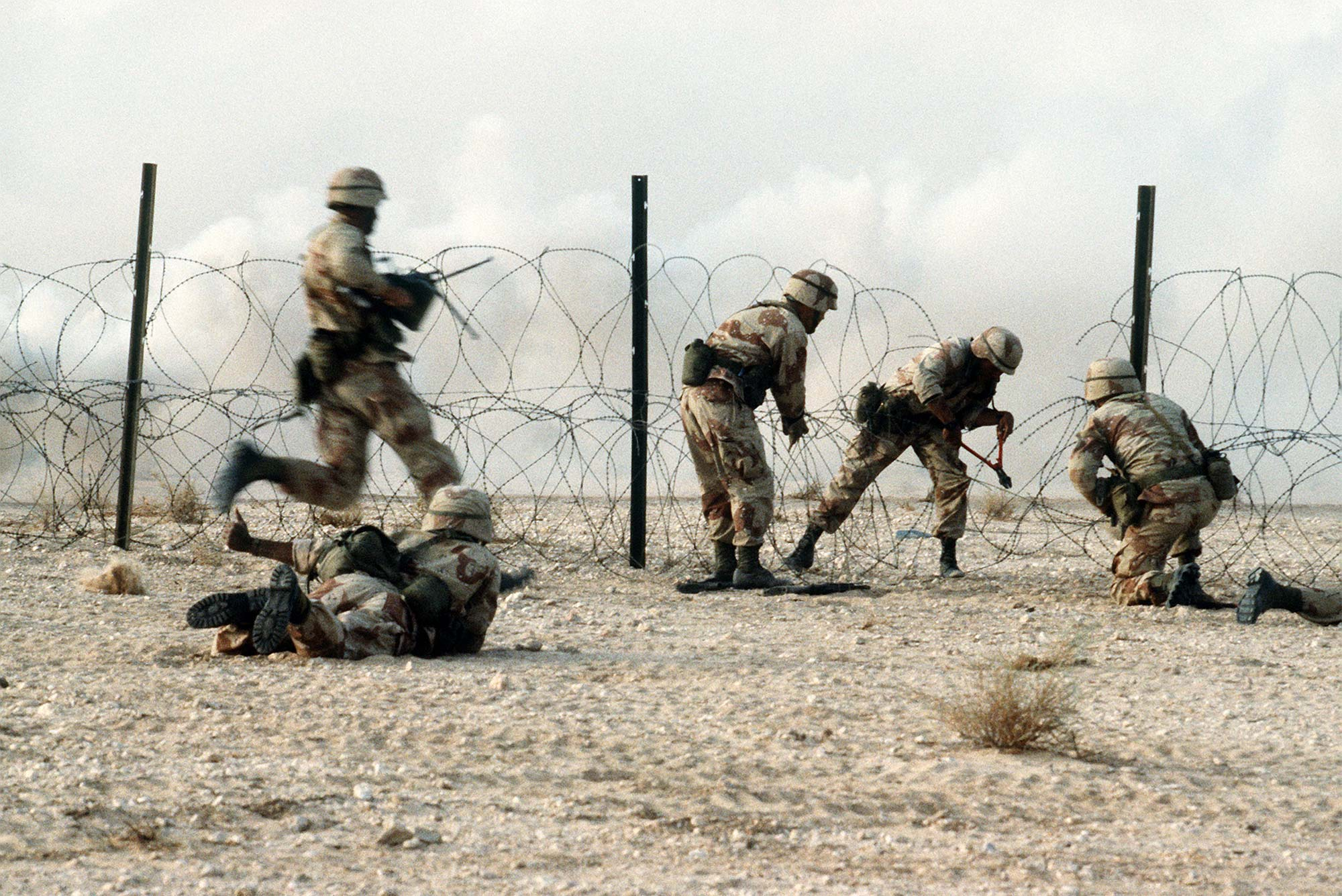 Members of the 1st Battalion, 325th Airborne Infantry Regiment, make their way through concertina wire during a live fire demonstration during Operation Desert Shield.