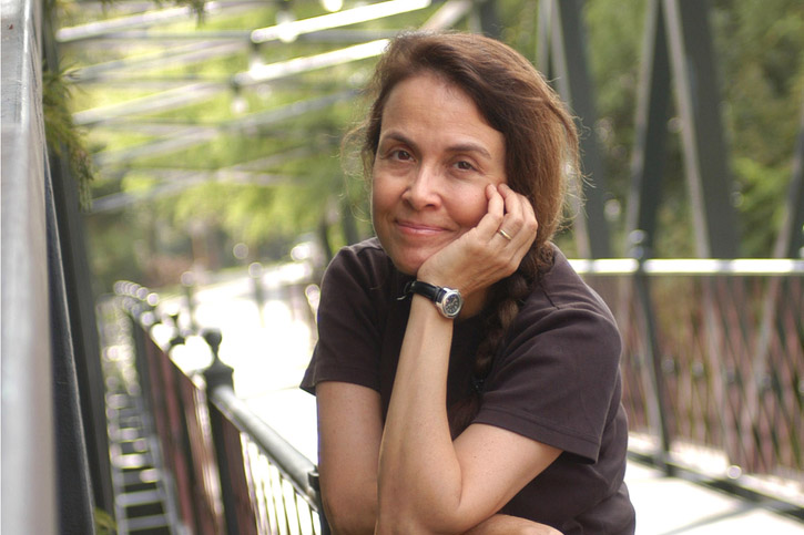 Poet Naomi Shihab Nye smiles for a photo while standing on a bridge
