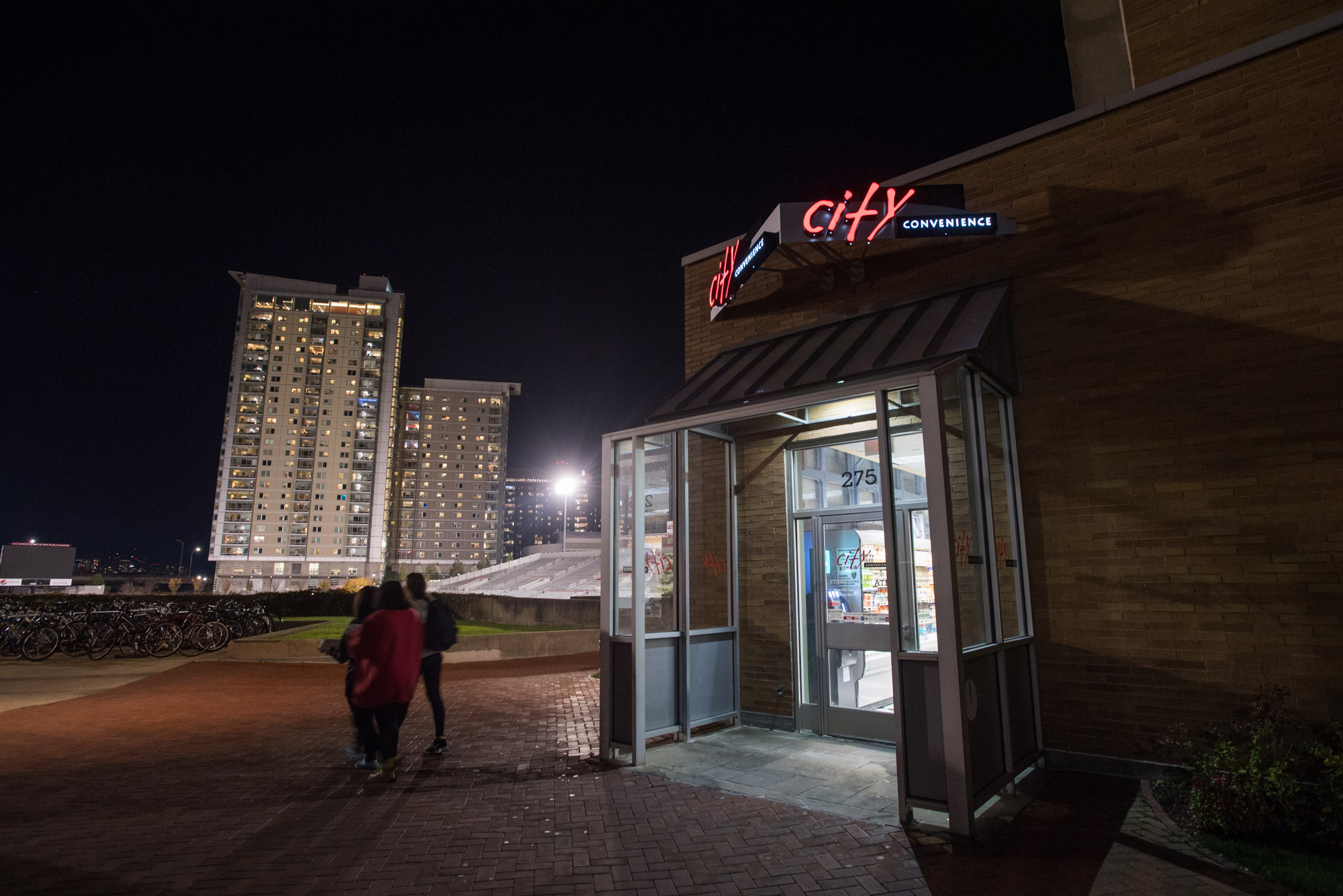 people walk out of City Convenience late at night