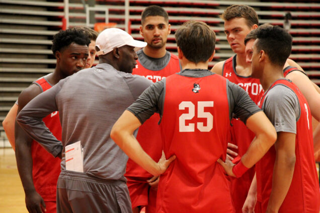 Men's basketball team huddles up around their coach during practice