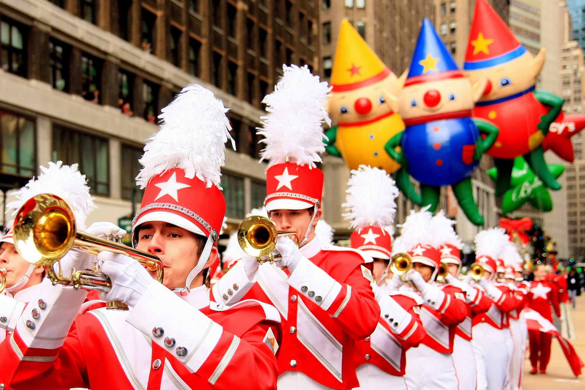 A group of trumpet players marches during the Macy's day parade with balloons floating in the distance
