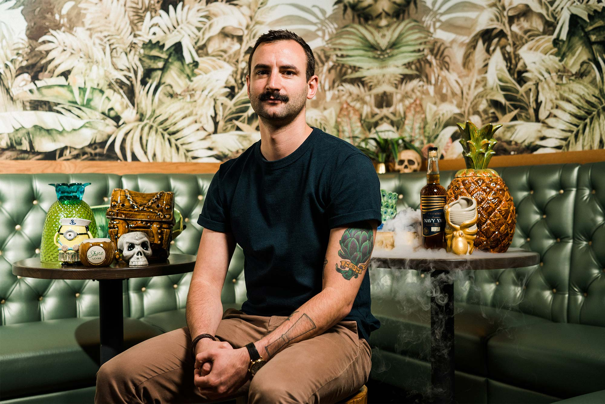 Portrait of Ryan Lotz, Beverage DIrector at Shore Leave Boston tiki bar, sitting in a green banquette surrounded by tropical wallpaper and tiki culture decoration. Photo by Chris McIntosh