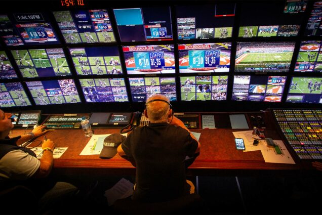 View over the shoulders of sports broadcasting director Bob Fishman watching the screens in the truck while directing an NFL broadcast