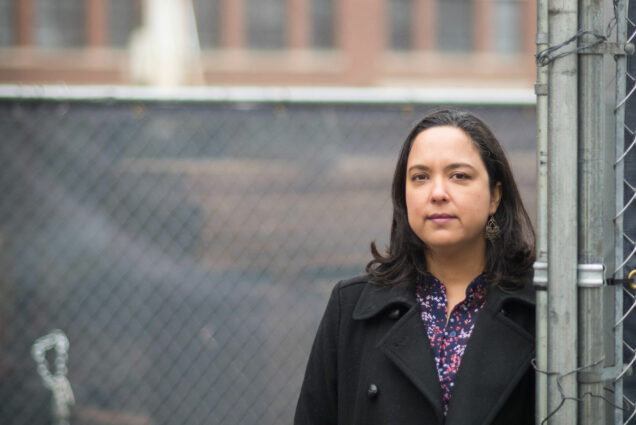 Portrait of Diana Ceballos, Boston University School of Public Health assistant professor of environmental health, in front of a Boston construction site.