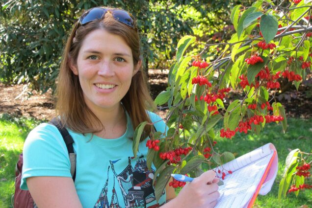 Ecological researcher Amanda Gallinat takes notes about tree fruit.
