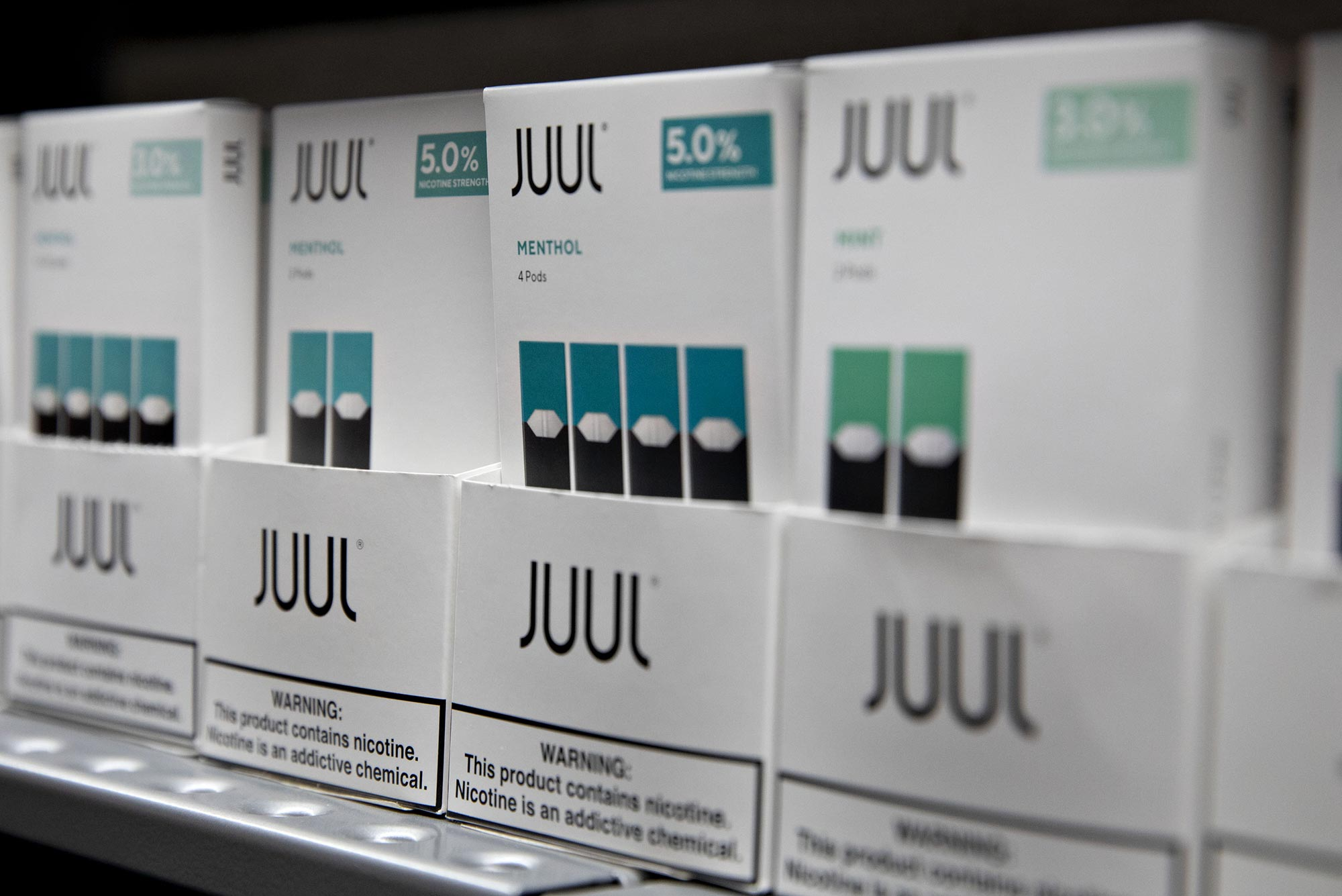 Packs of JUUL e-cigarettes on a display shelf focused on a pack of Menthol flavored vape package.