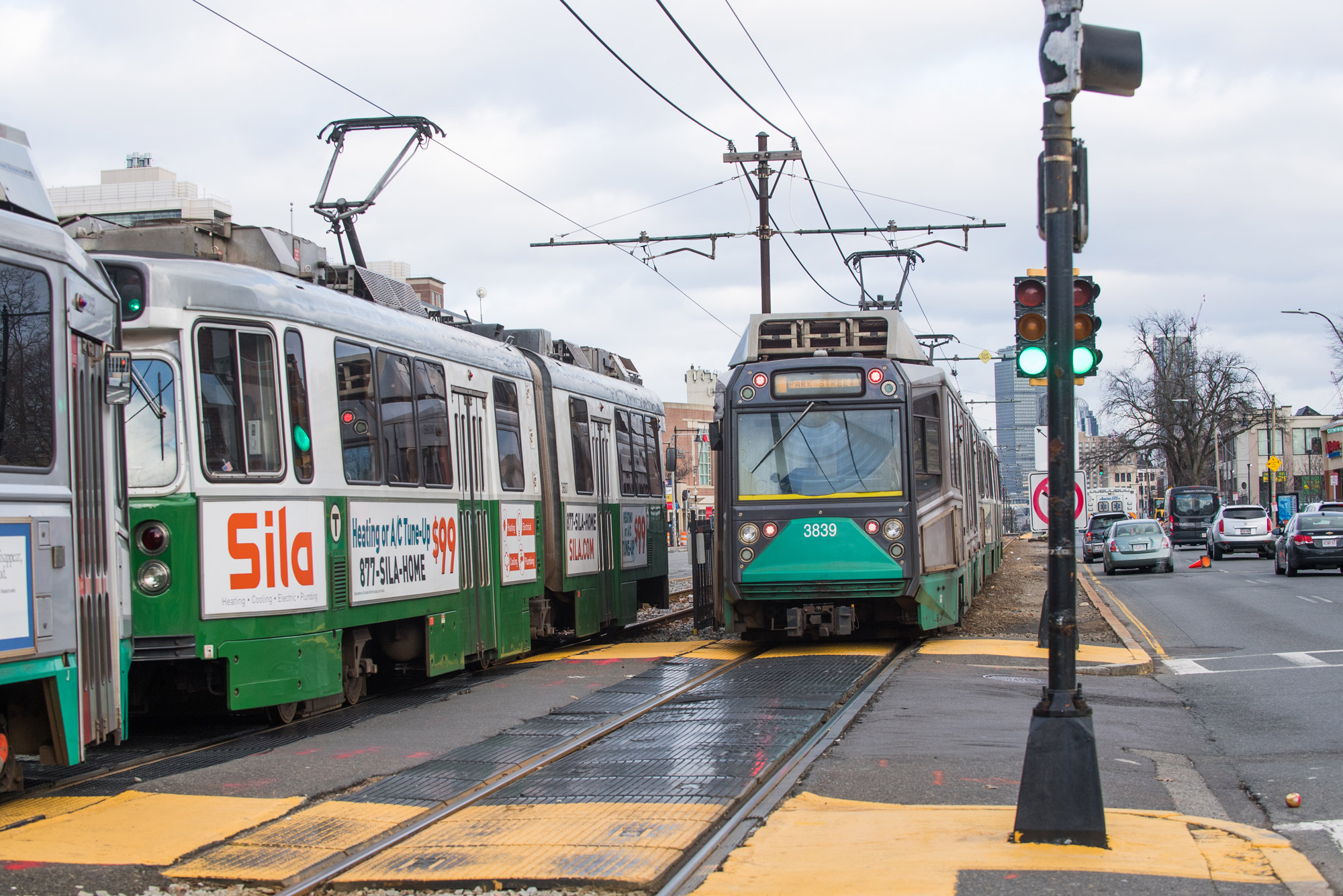 Two greenline MBTA trains pass along Commonwealth Avenue.