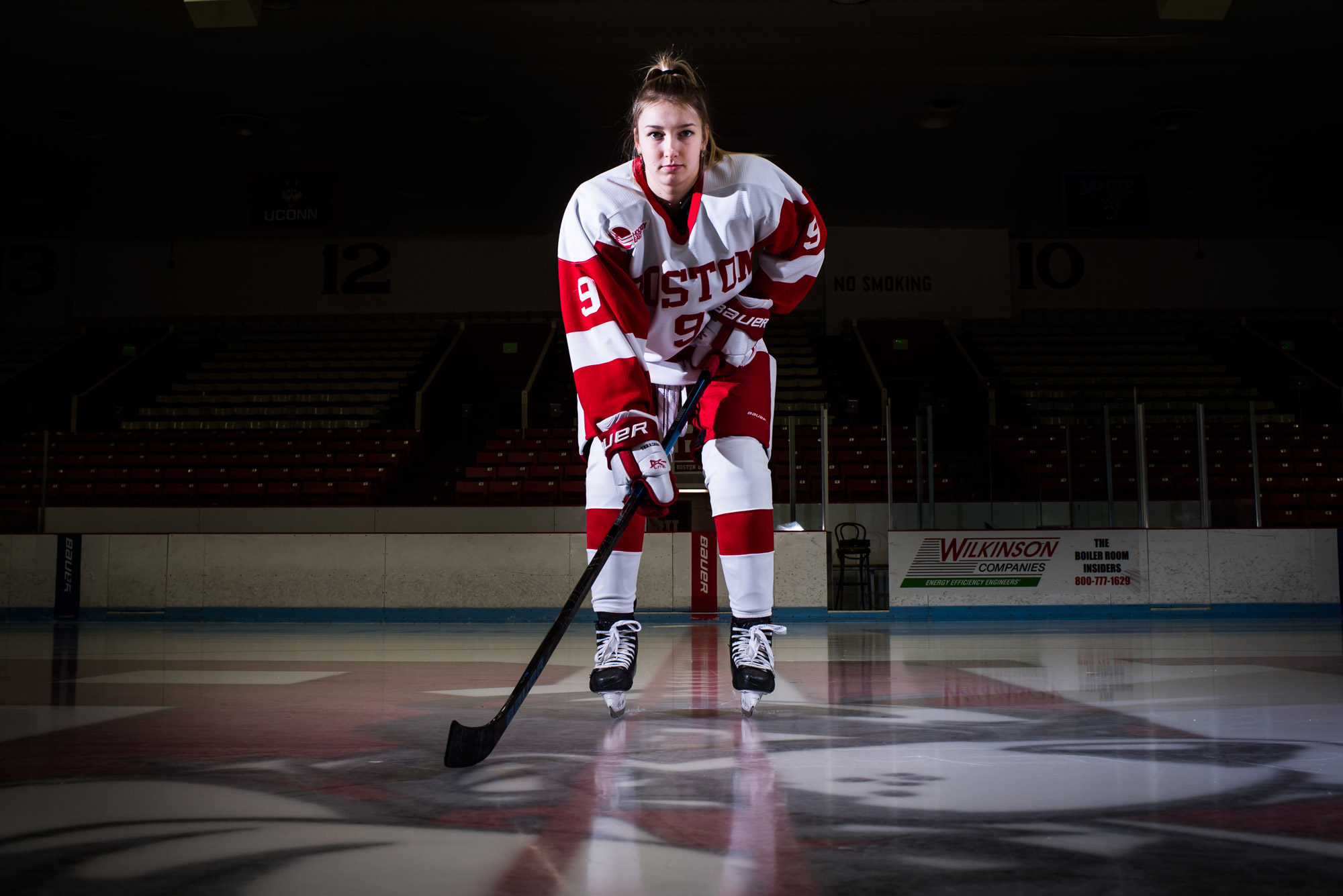 Abby Cook poses for a photo on the ice while wearing her hockey uniform