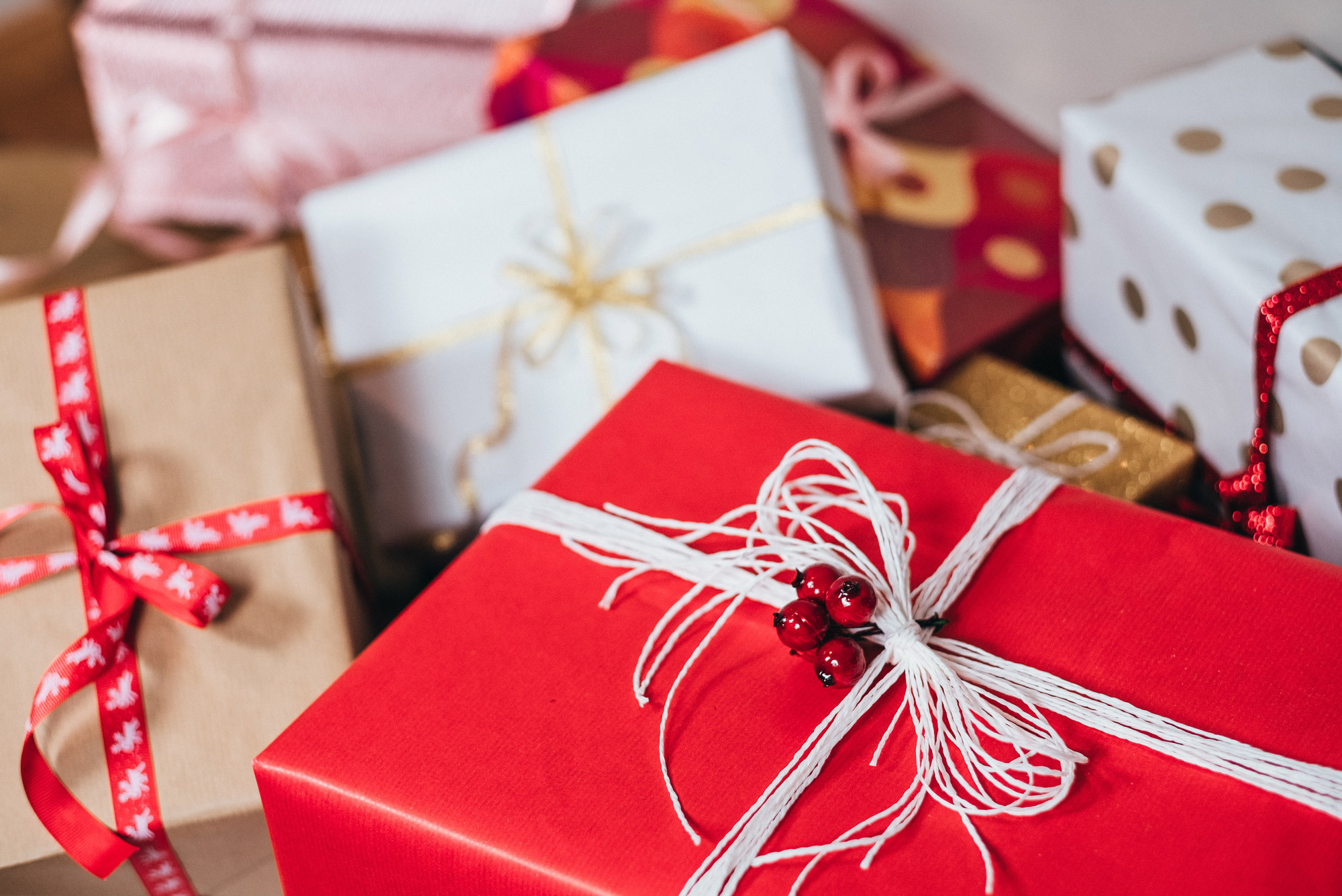 wrapped holiday presents in red, gold, and white