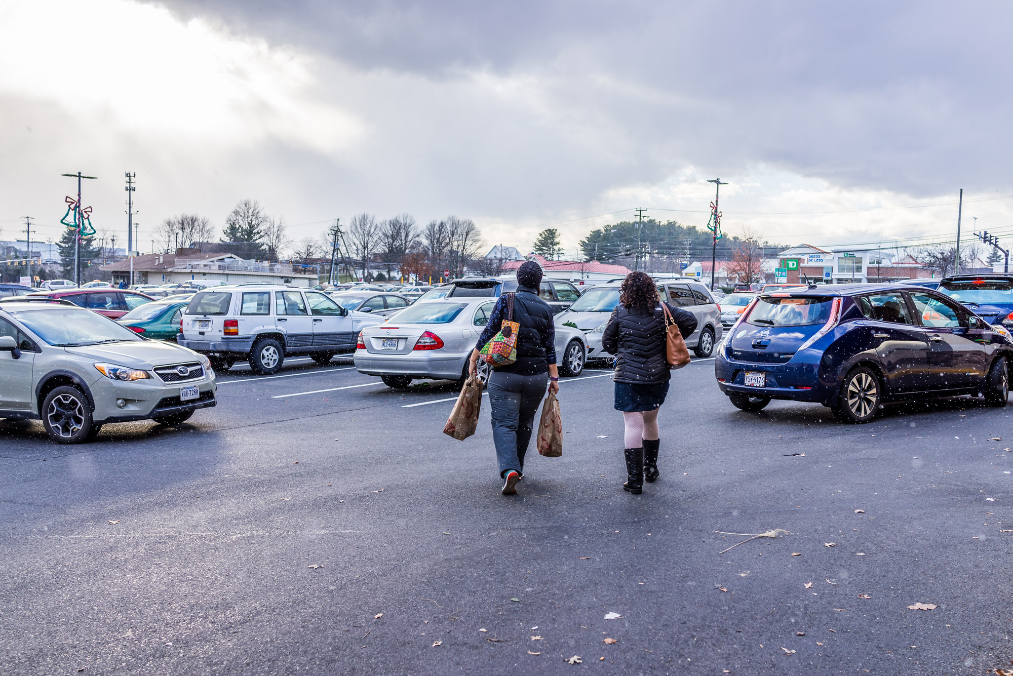 Two women walk through a crowded parking lot while it is snowing