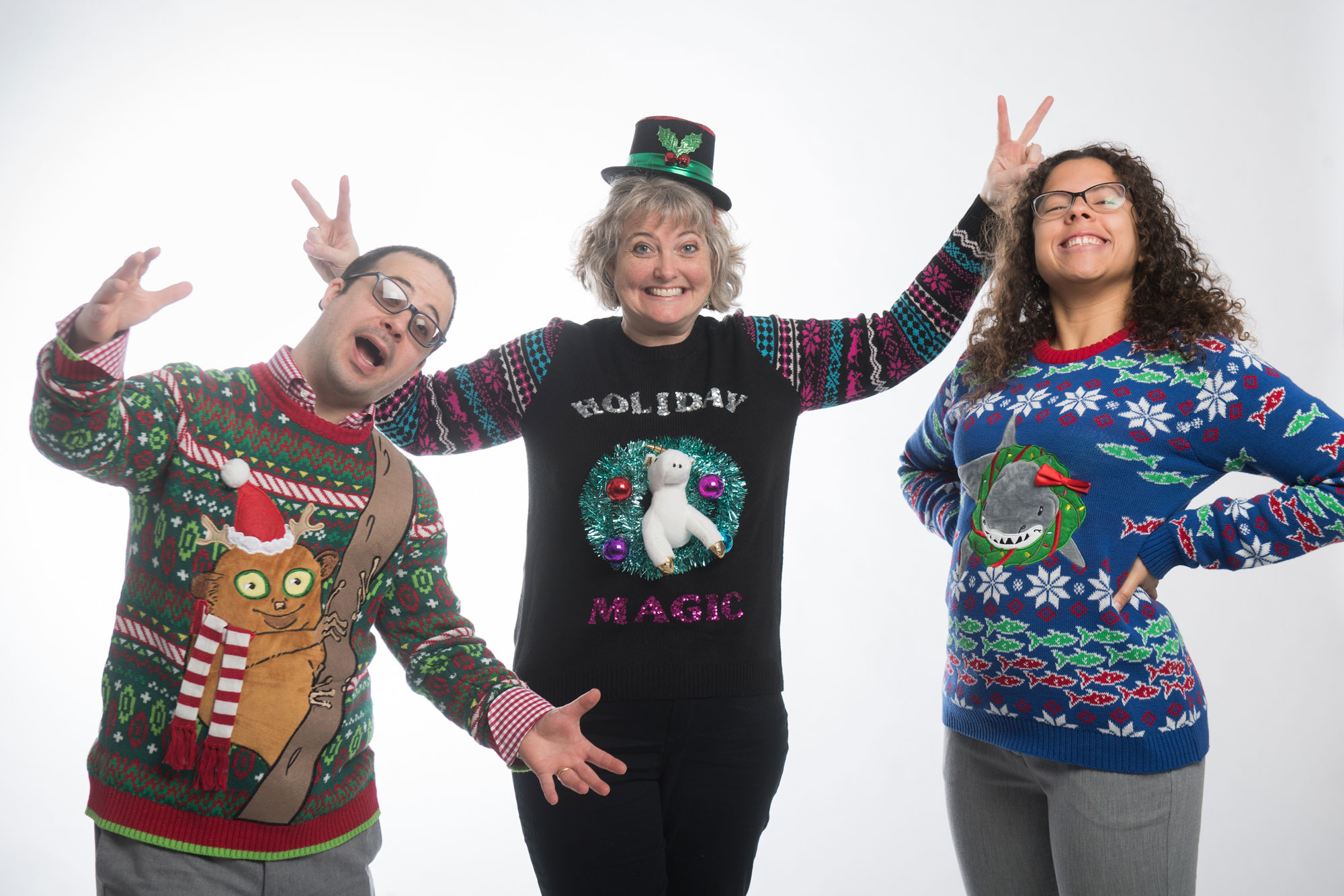 3 people pose in their ugly holiday sweaters