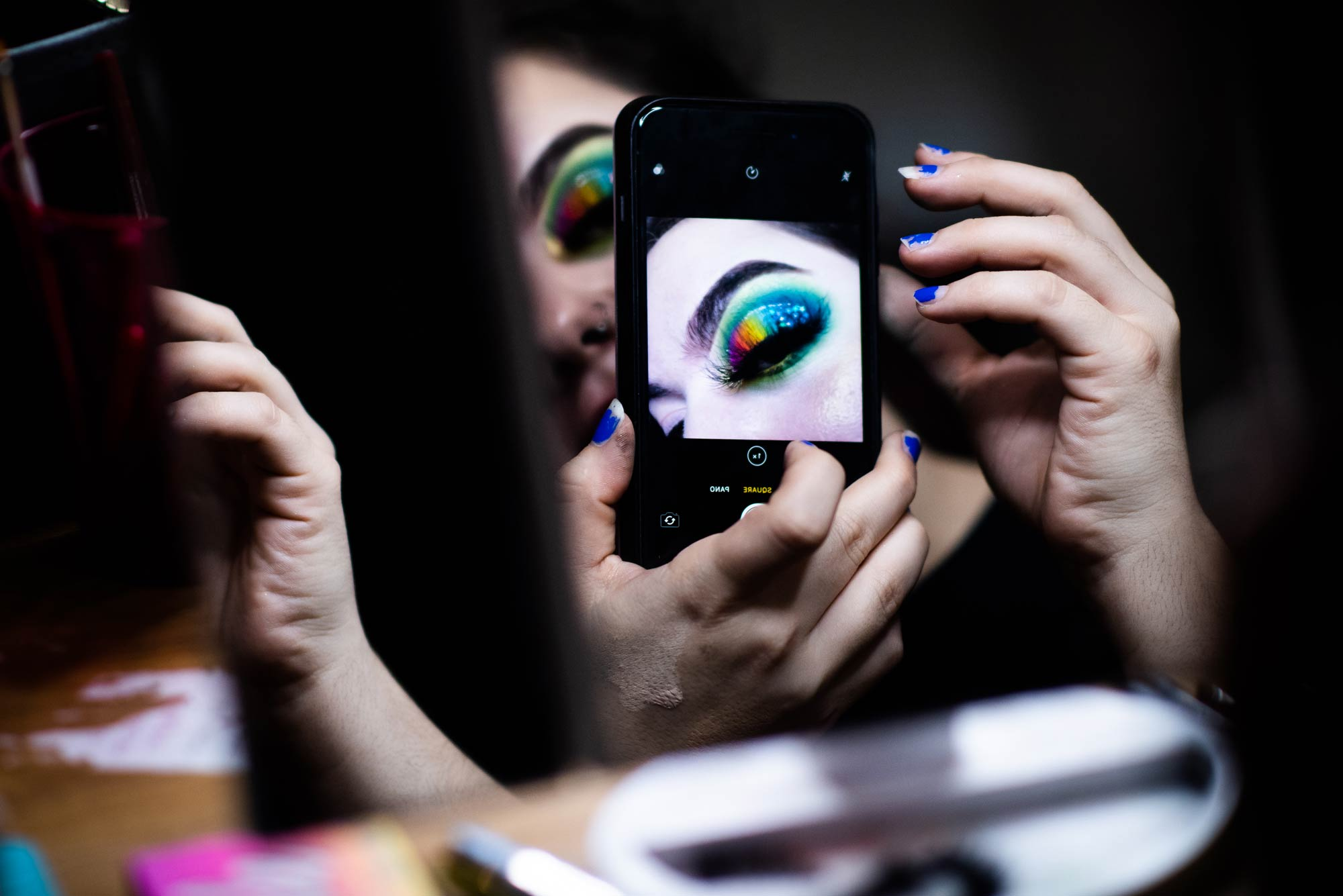 A woman wearing make up takes a photo of her eye with an iPhone.