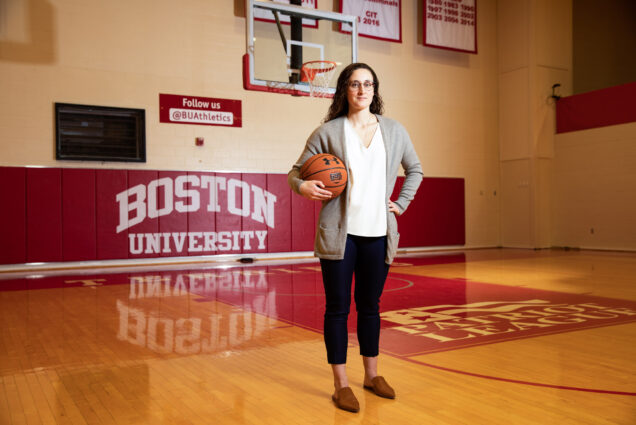"A portrait of Sarah Hope (COM'17) standing with a basketball in front of signs reading ""Boston University"" and ""Follow Us @BUAthletics."""