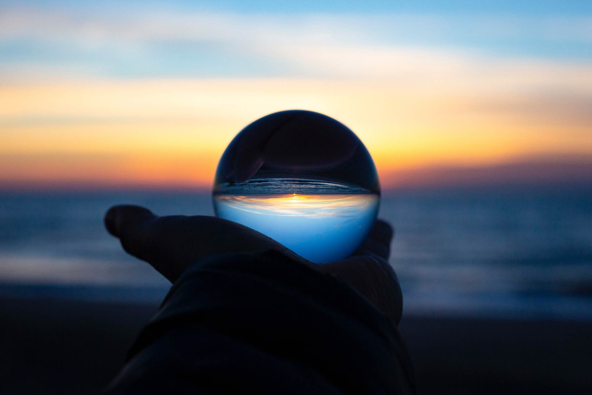 A photo of a hand holding a crystal ball that is reflecting a skyline.