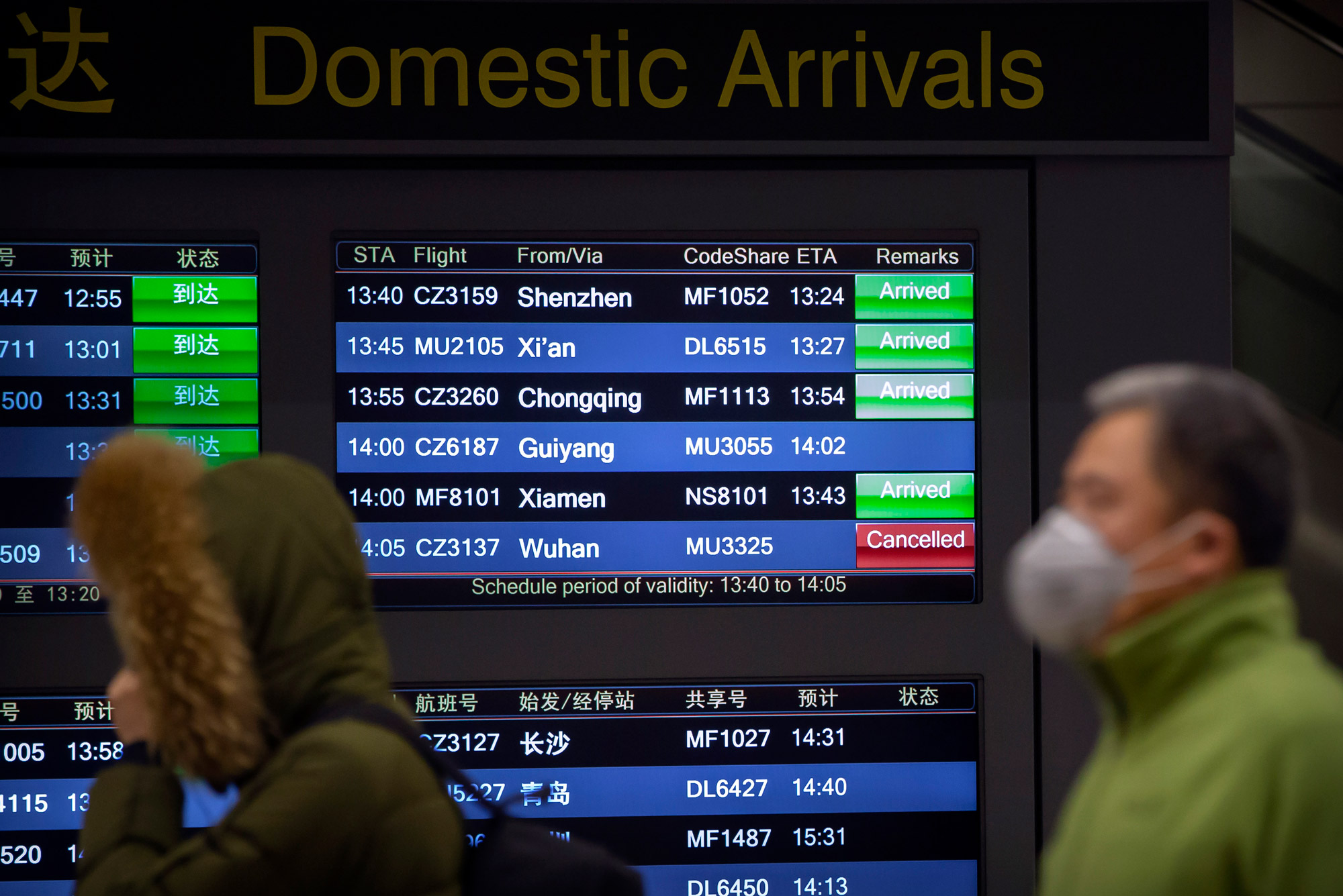 Travelers walk past a display board of arriving flights showing a canceled flight from Wuhan at Beijing Capital International Airport in Beijing.