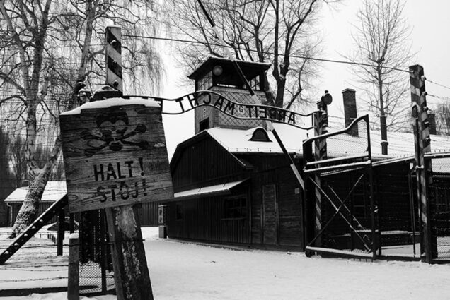 "An image of Auschwitz. A sign in the foreground reads ""Halt! Stoj!"""