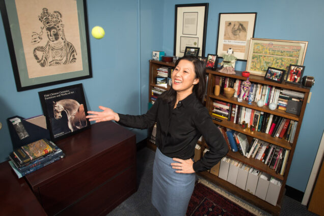A photo of Alice Tseng standing in her office throwing a tennis ball up in the air.
