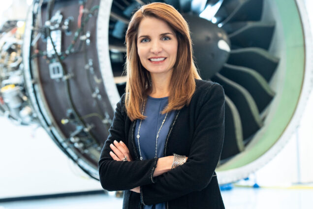 Jill Albertelli poses for a portrait in front of a jet engine.