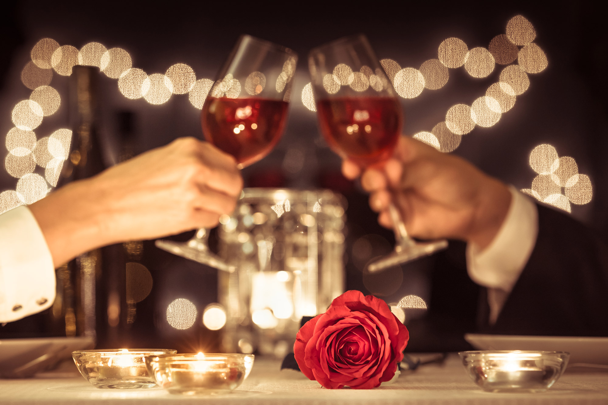 A photo of two people clinking wine glasses.