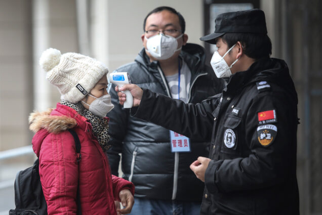 Security personnel check the temperature of a passenger in the Wharf at the Yangtze River on January 22, 2020 in Wuhan, Hubei province, China.