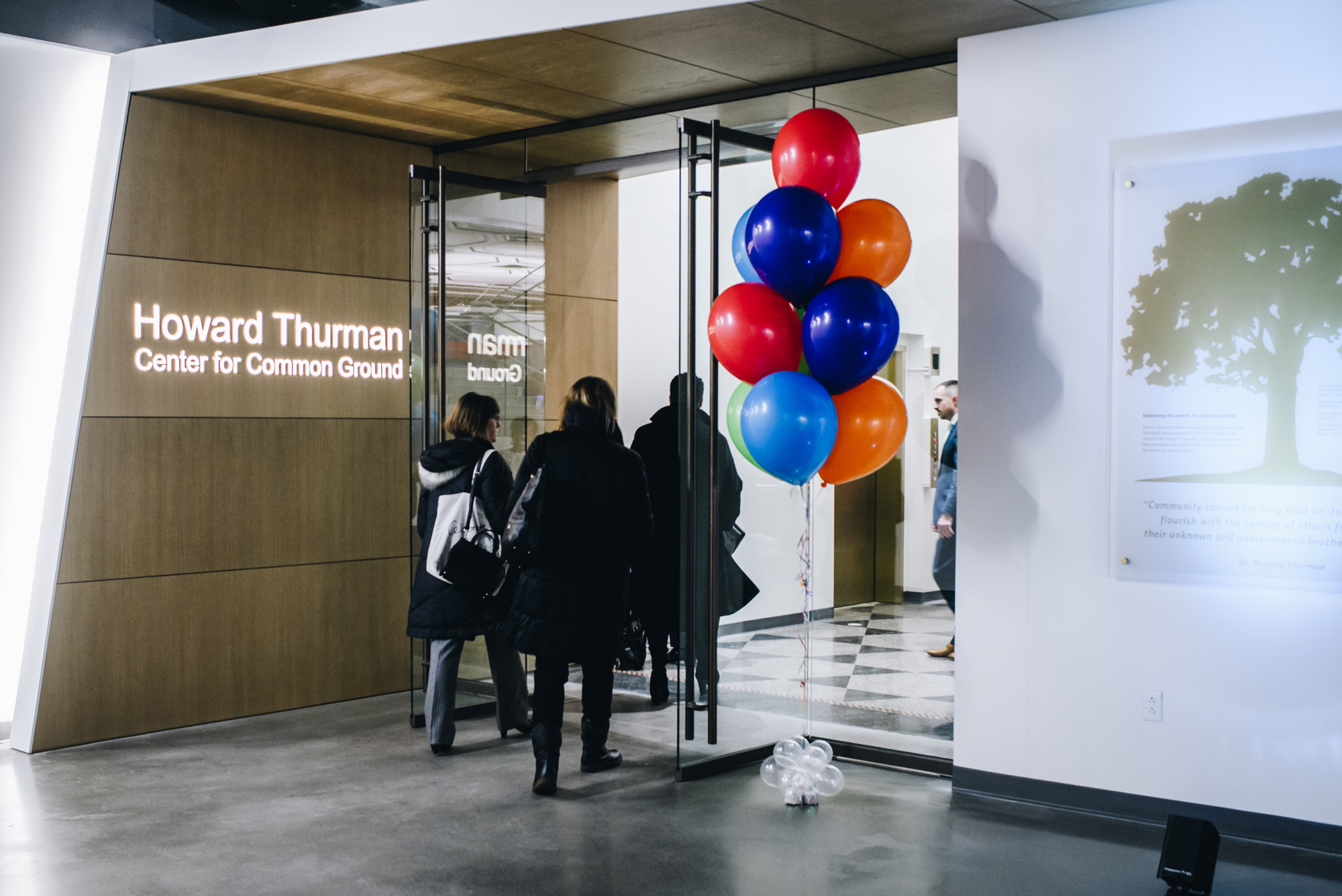 People walk into the brand new Howard Thurman Center during the grand opening. Colorful balloons mark the entrance.