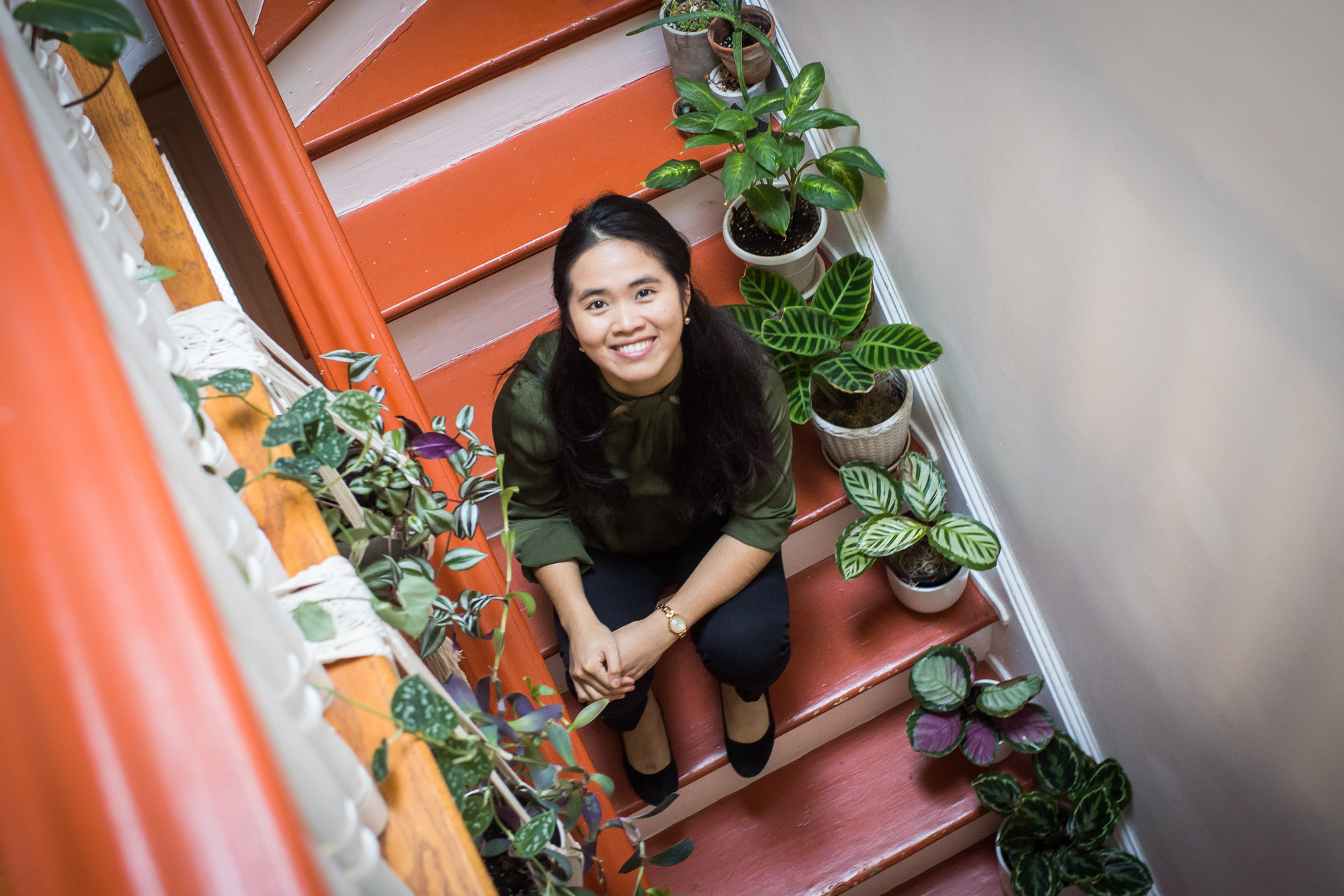 Minh-Thuy Nguyen sits on orange stairs lined with all of her plant babies
