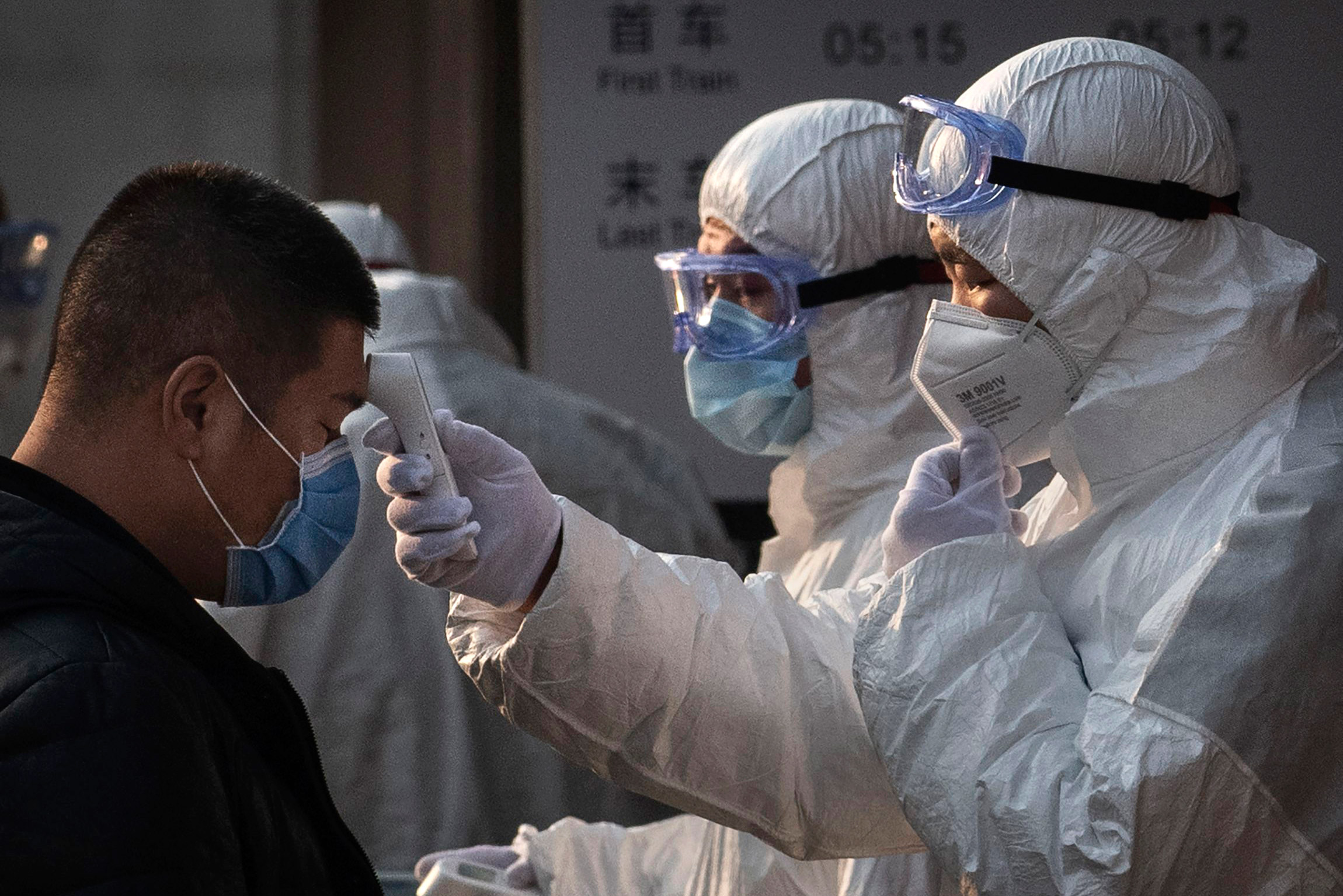 Chinese health workers in white suits, check the temperatures of Chinese residents