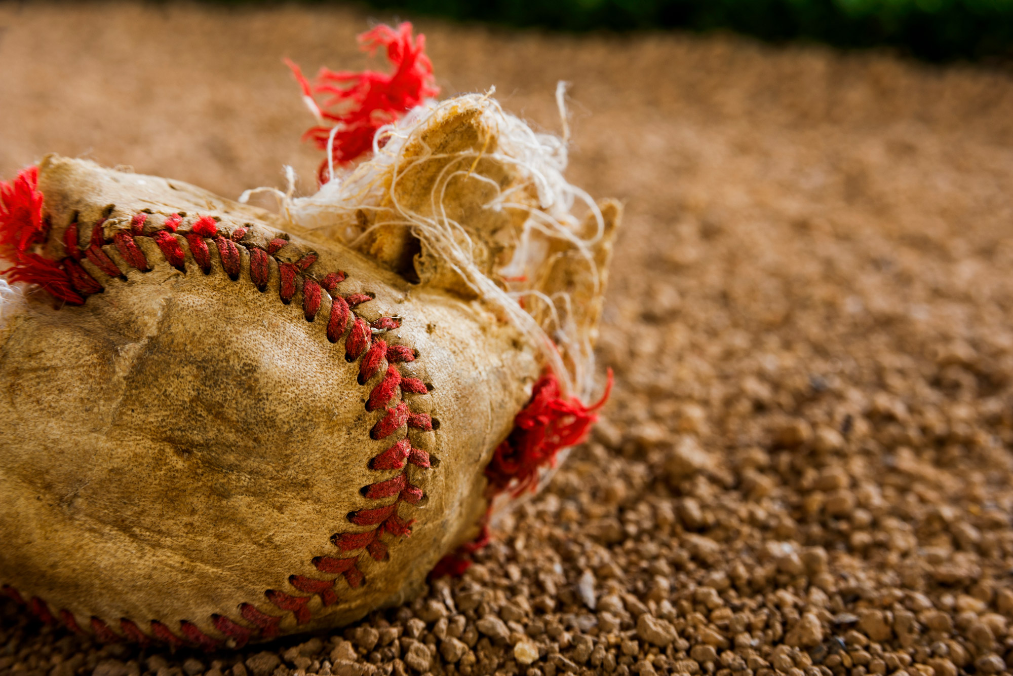 A destroyed baseball lays on the ground