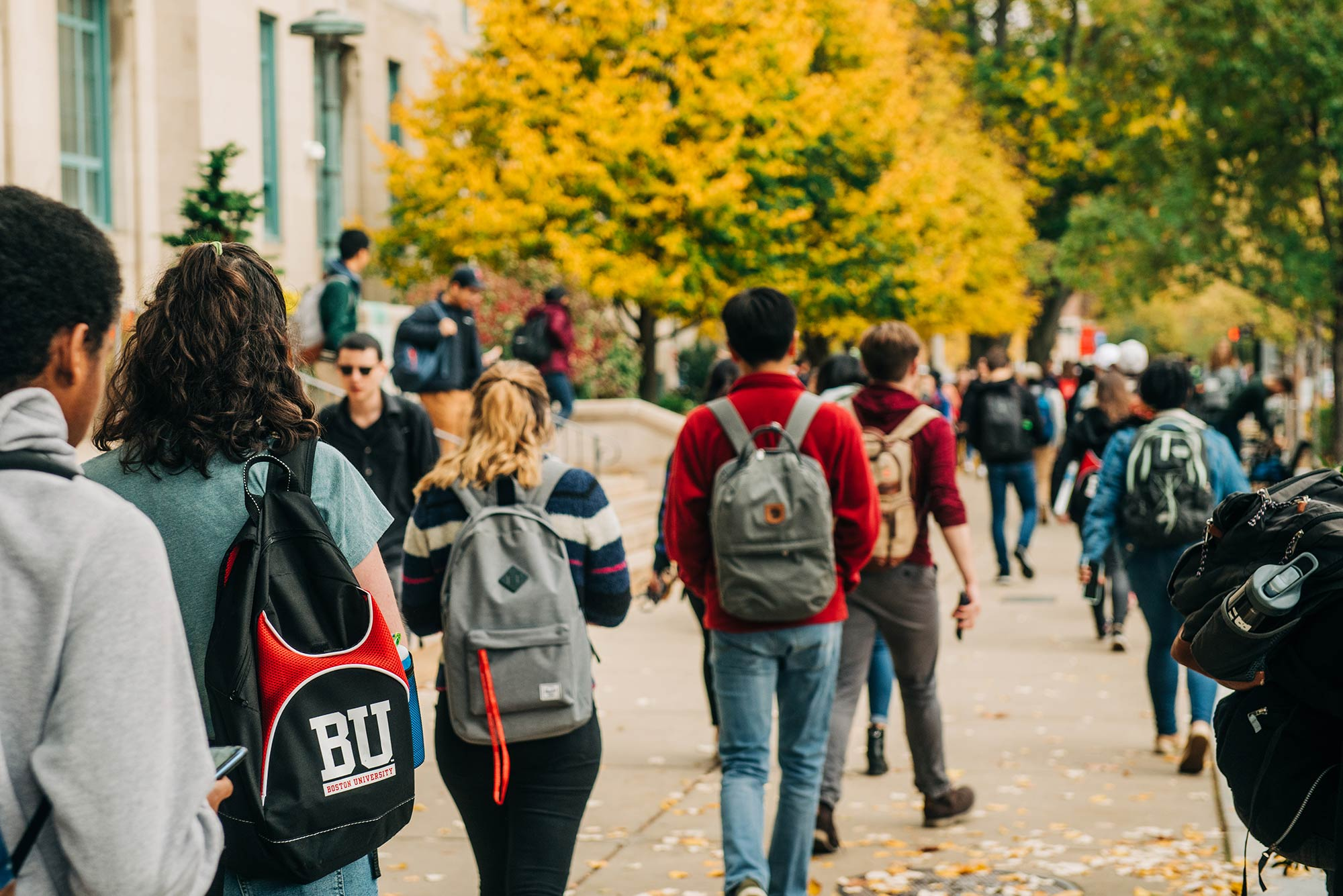 A crowd of Boston University students walk along Commonwealth Avenue on the BU Charles River Campus