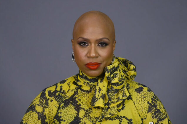 A portrait of Ayanna Pressley where she reveals her bald head as a result of Alopecia Areata
