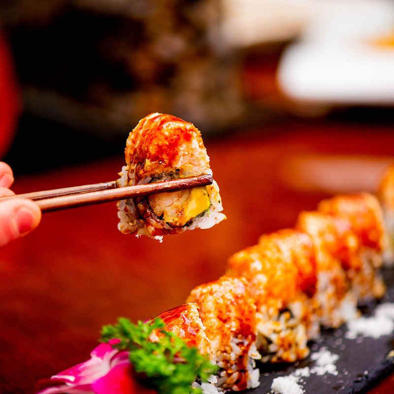 Photo of person holding up sushi with chopsticks with a plate of sushi in the background.
