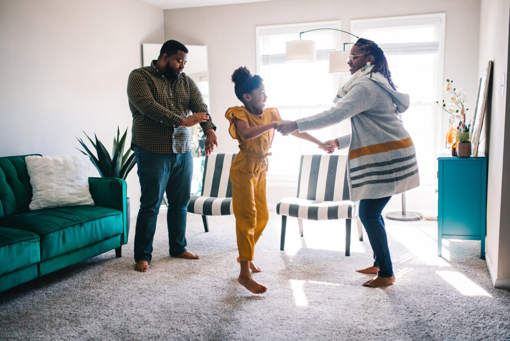 A photo of Joshua Reynolds (CFA'11, MET'13) and Danielle Galloway (CAS'15) dancing with Danielle's daughter Melody, age 7.