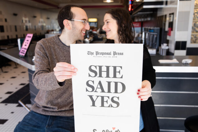 "A photo of Rick Sobey (COM'12) and Felicia Gans (COM'17) holding a mock newspaper and a headline asking ""Felicia, Will You Marry Me?"""