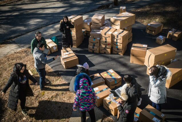 A photo of Shishong Chen, a law student from China, and other students organizing boxes that will be shipped to China.