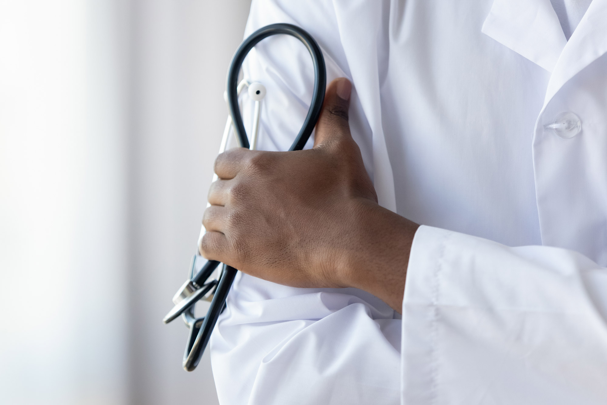A photo of a doctor holding a stethoscope against their white lab coat.