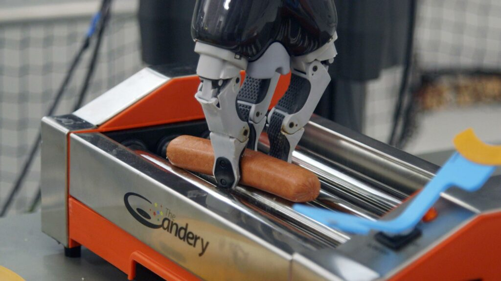 An AI robotic arm places a hot dog on a hot dog cooker.