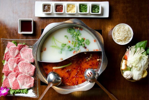 Overhead photo of hot pot with dishes of vegetables, meat slices, and toppings around the central pot.