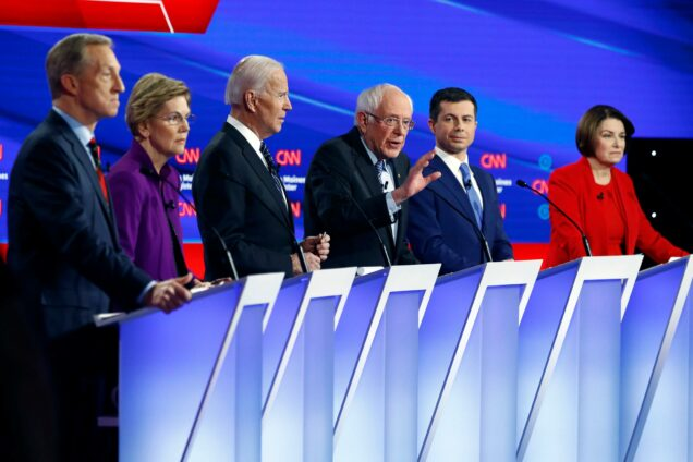 2020 Democratic Presidential candidates Tom Steyer, Elizabeth Warren, Joe Biden, Bernie Sanders, Pete Buttigieg, and Amy Klobuchar on stage during the Iowa Democratic Debate.