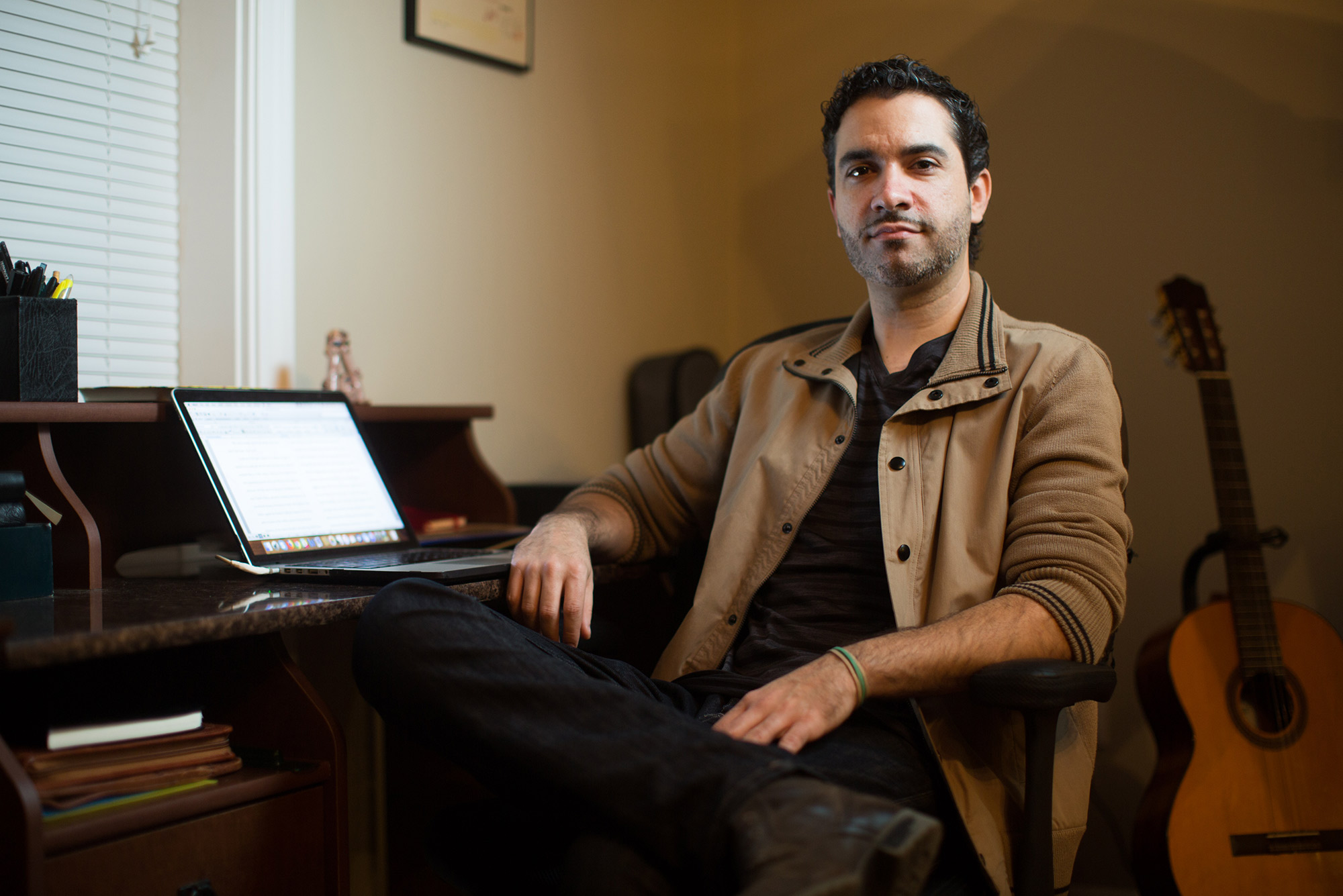 Writer and novelist Dariel Suarez (CFA'12) sits in his office with his laptop open on a desk behind him.