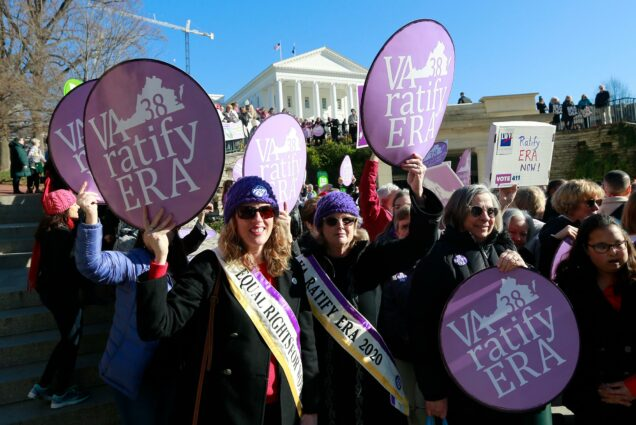 "Equal Rights Amendment supporters hold signs with ""VA Ratify ERA"" outside the Virginia State Capitol in Richmond."