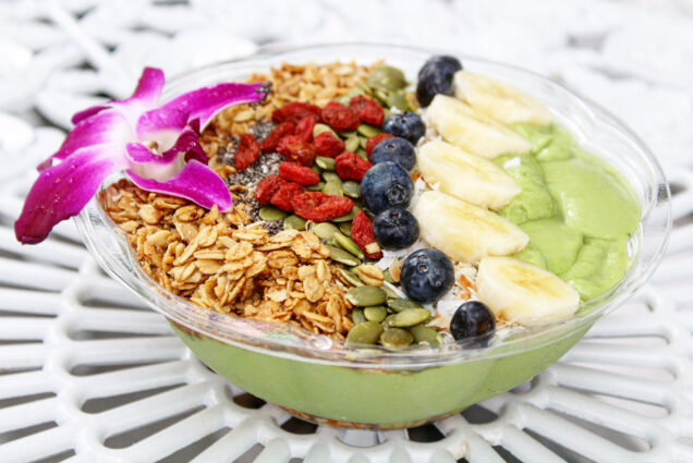 Acai bowl with granola, seeds, and fruit; garnished with a flower.