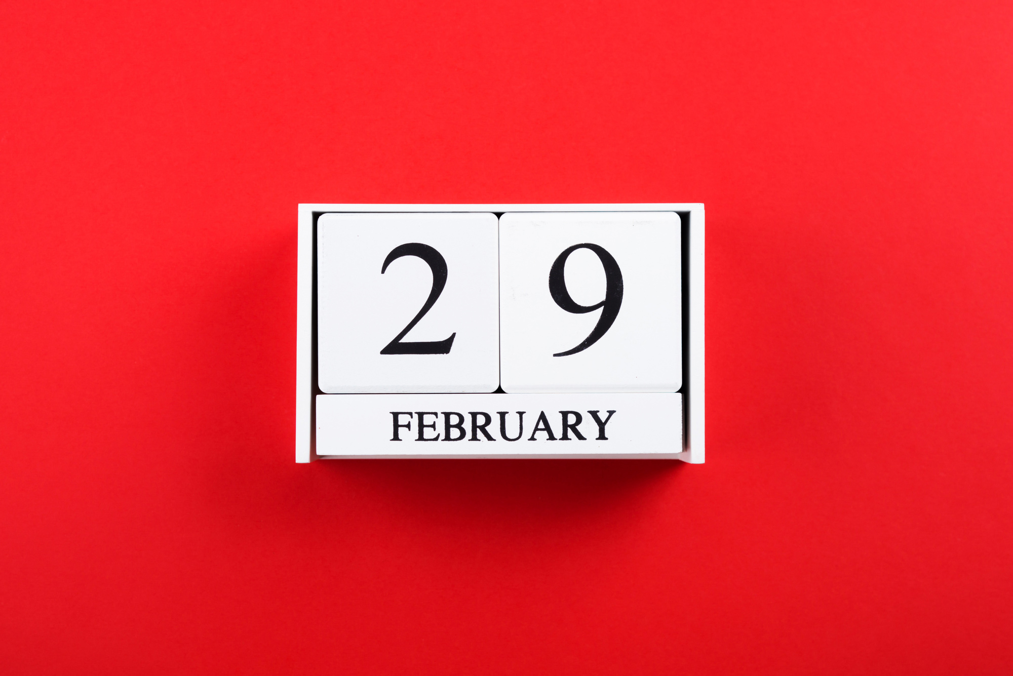 Image of white blocks on a bright red background; blocks say February 29.