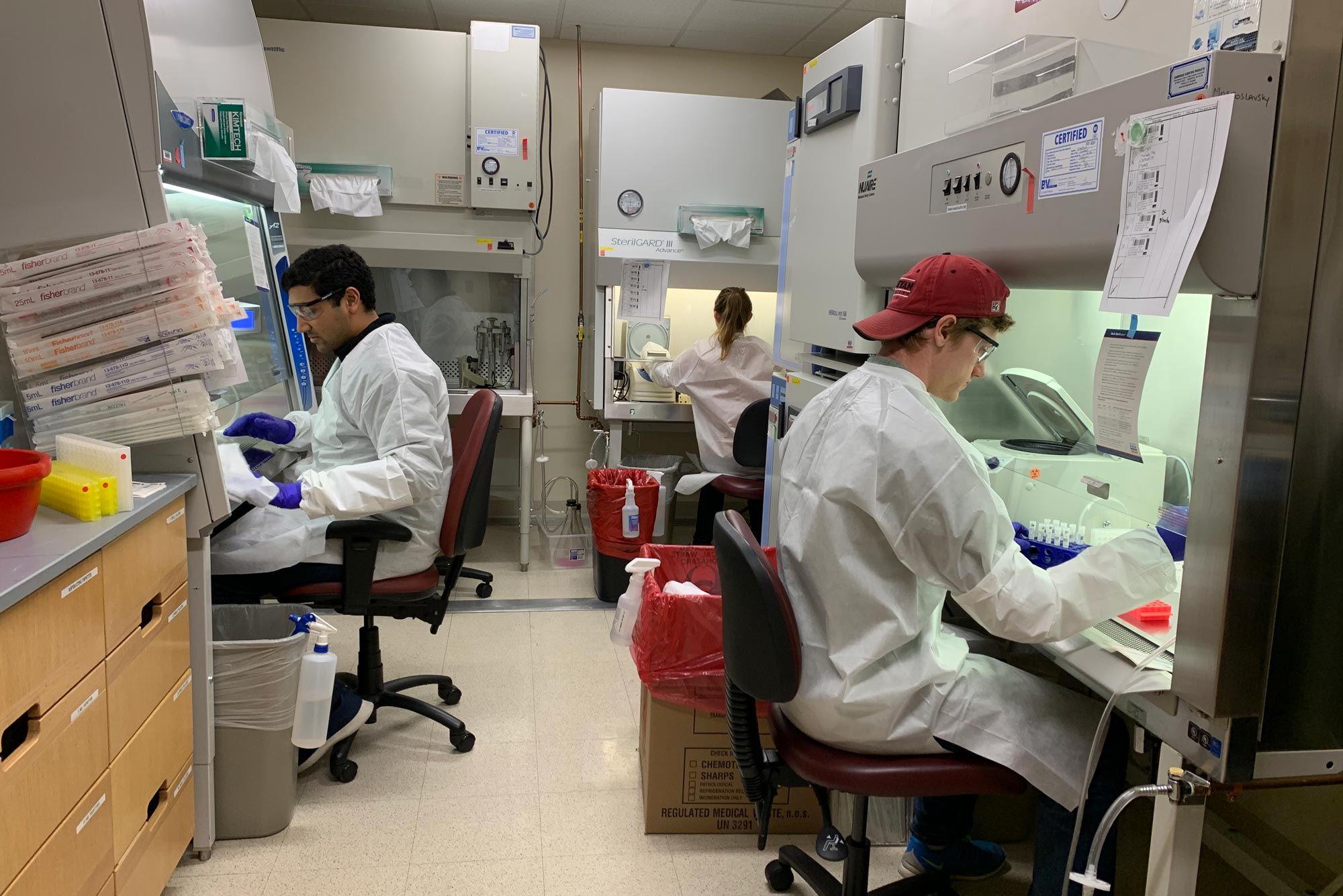 Center for Regenerative Medicine researchers Aditya Mithal, Claire Burgess, and Andrew McCracken prepare samples collected from Boston Medical Center patients suspected to be infected with the novel coronavirus.