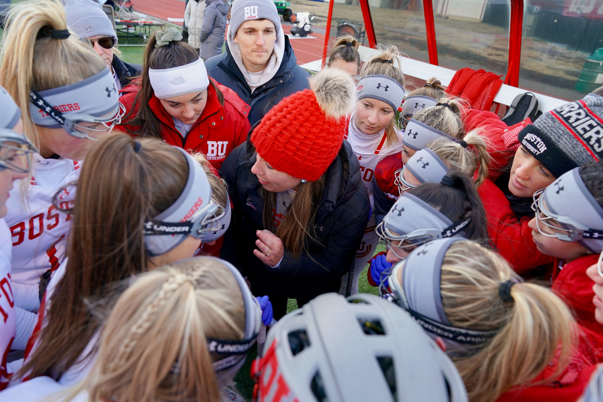 A photo of the Boston University women's lacrosse team in a huddle