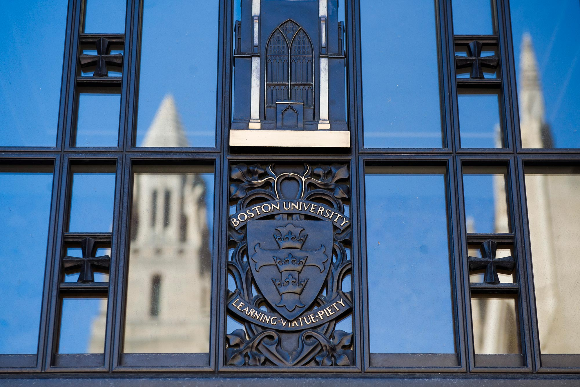 "Photo of the entrance to STH with the BU Logo (""Boston University, Learning, Virtue, Piety"") with the CAS tower reflected on the left and right."