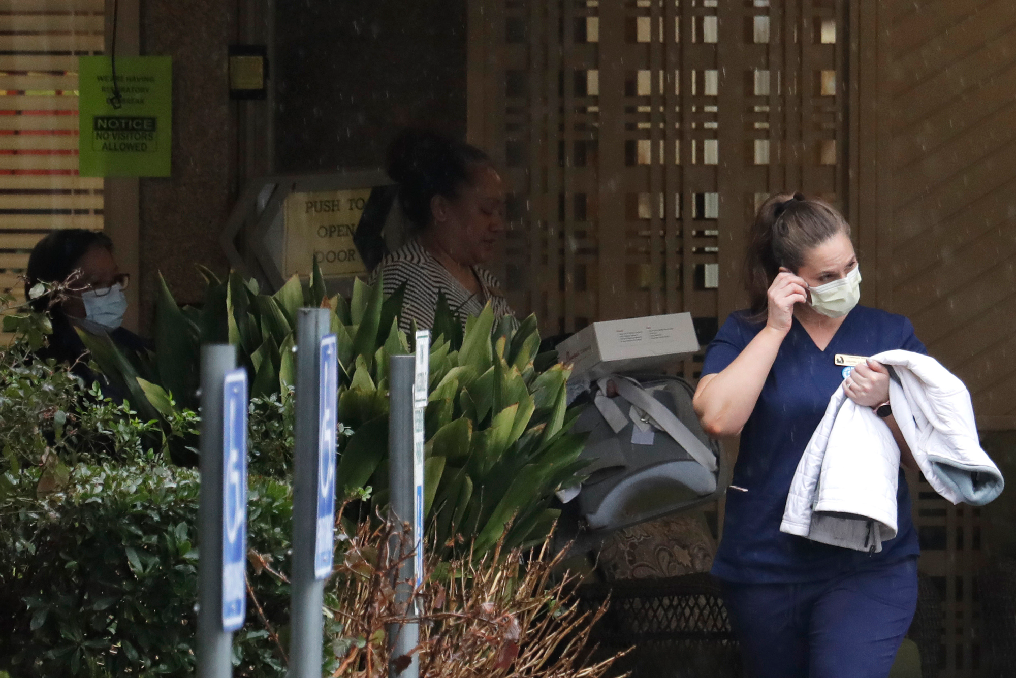 A worker at the Life Care Center in Kirkland, Wash., near Seattle, wears a mask as she leaves the building