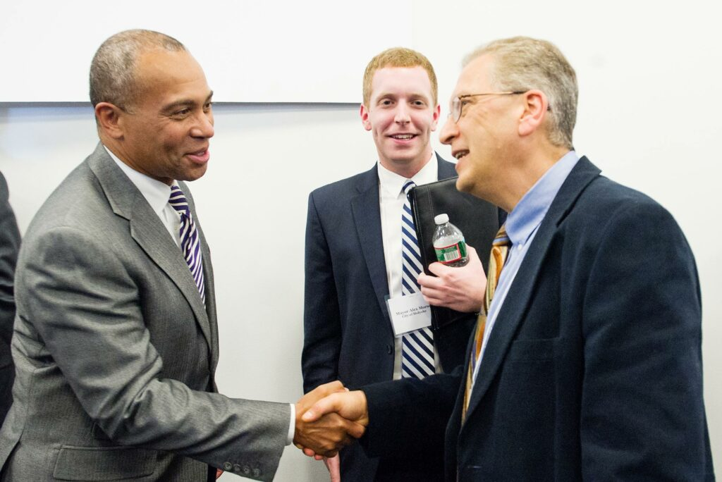 Photo of Professor Azer Bestavros shaking hands with Governor Deval Patrick as Holyoke mayor, Alex Morse looks on at the Massachusetts Green High Performance Computing Center in Holyoke, MA in April 2014.