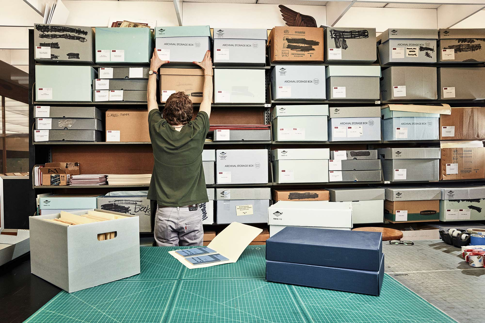 Photo of a student worker at the Howard Gotlieb Archival Research Center filing archive boxes.