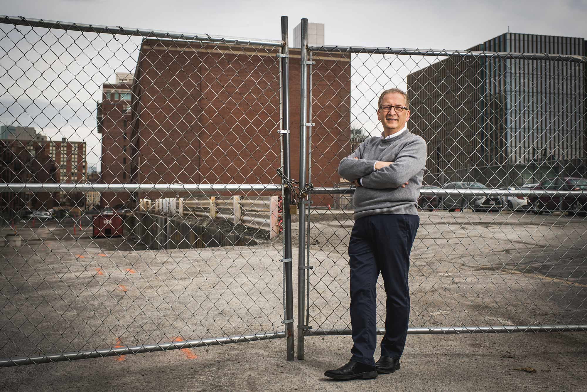 Portrait of Azer Bestavros who looks through a chain link fence towards the site of BU's new Data Sciences building.